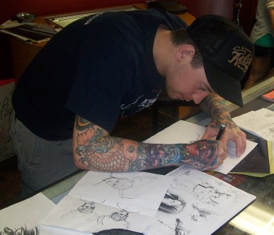 Josh prepping the stencil. The raw sketch is by his inked-up arm.