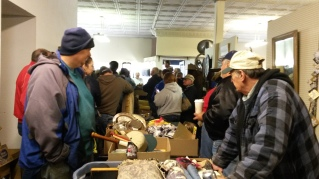 """Auction Day - Bidders crammed around the """"bag lots"""" in the 3-ring circus"""